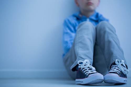 young child sitting against a wall