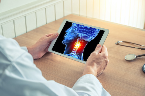 hands holding ipad with diagnostic image of head