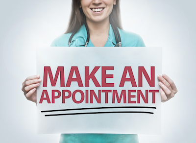 woman in scrubs holding sign that reads make an appointment