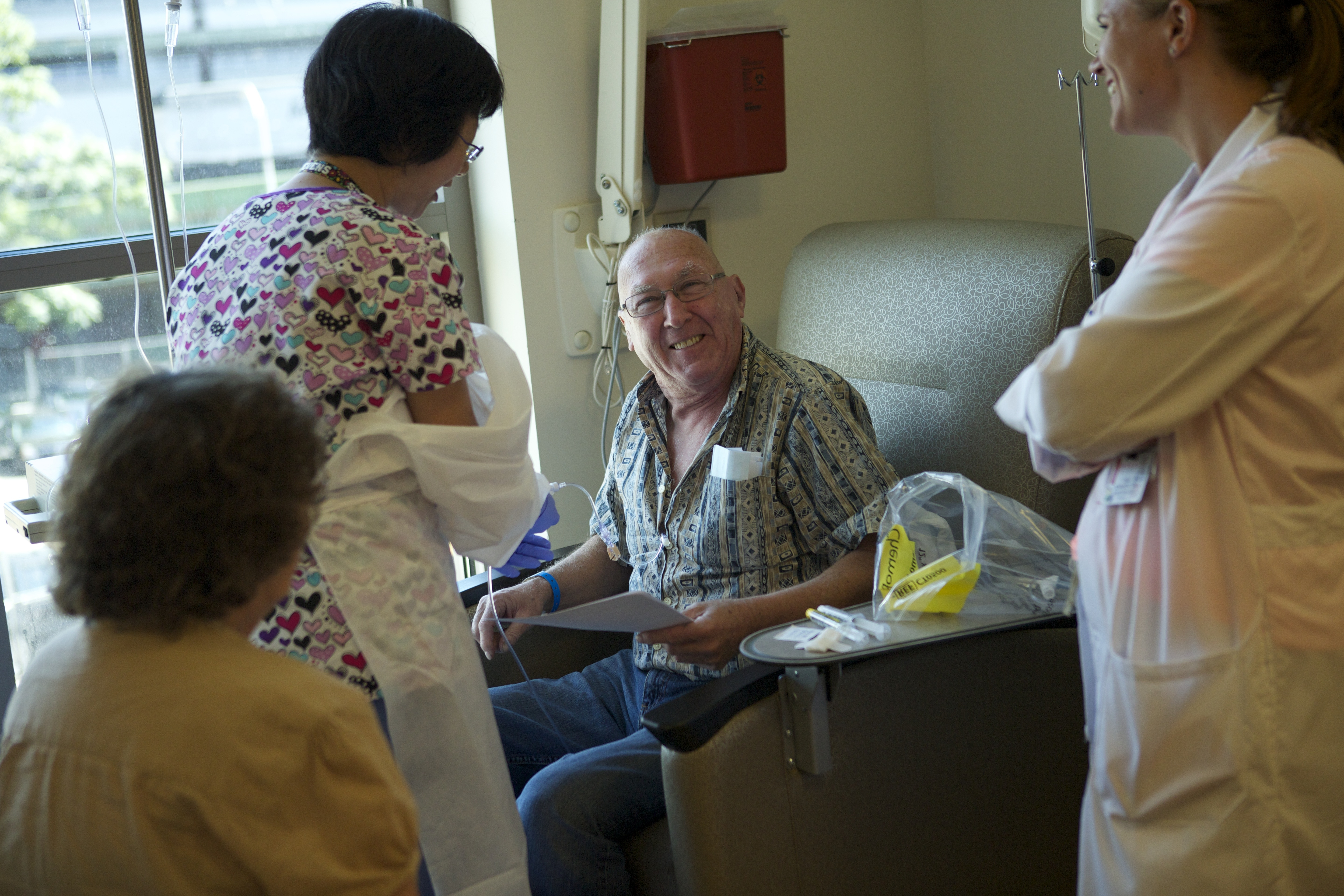 Smiling patient sitting in a chair surrounded by nurses