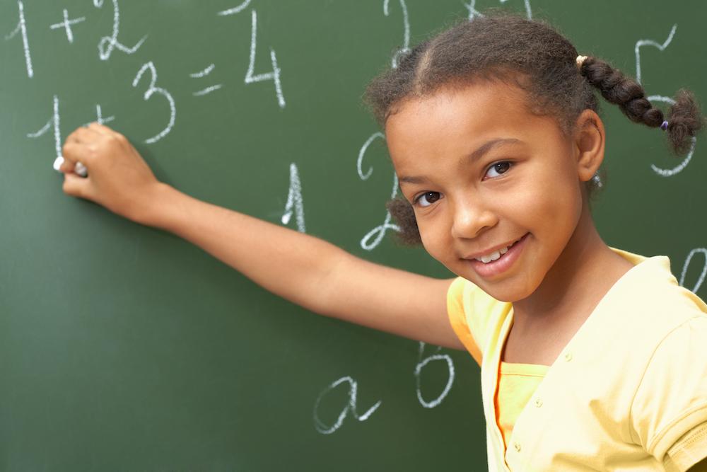 little girl standing by a chalkboard