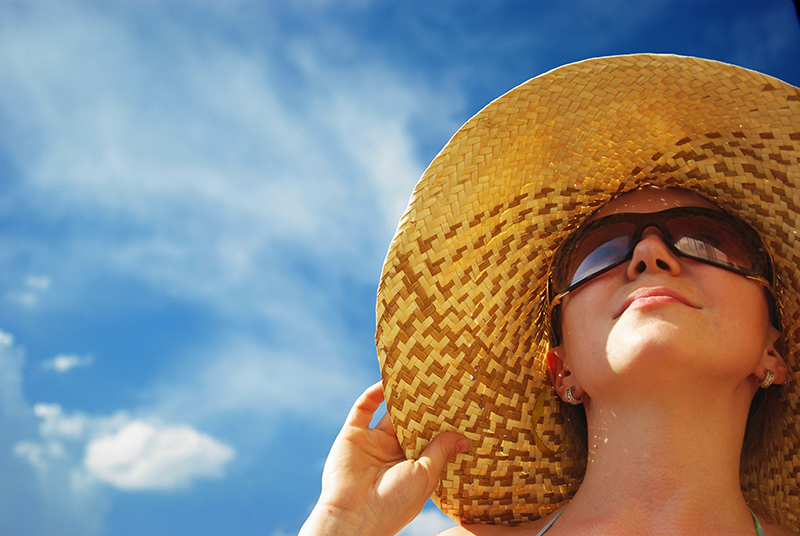 image of woman in sunhat under blue sky