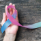 hands holding a blue and pink thyroid cancer awareness ribbon